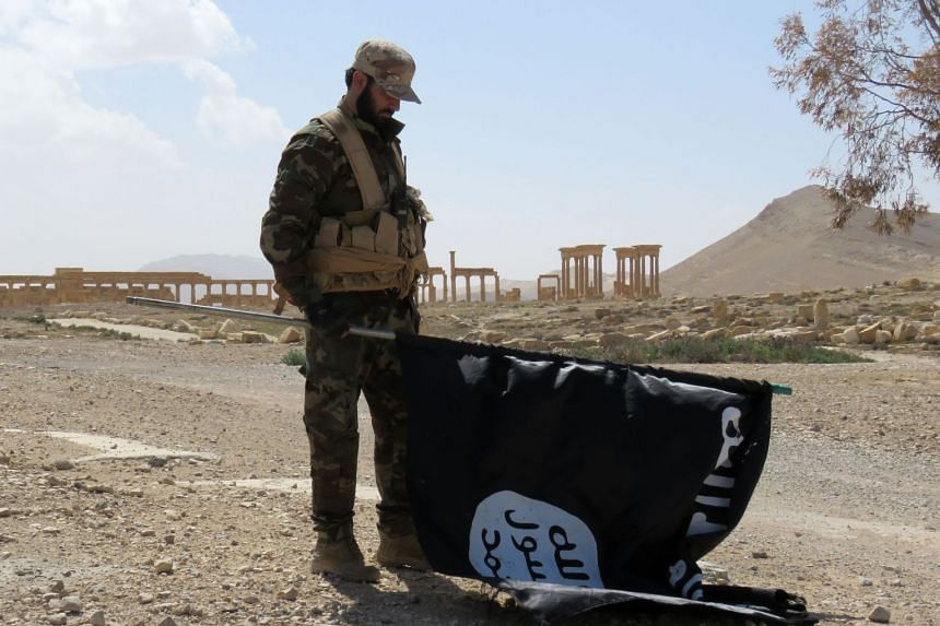 A member of the Syrian pro-government forces looking at an ISIS flag in Palmyra, Syria, in 2016.