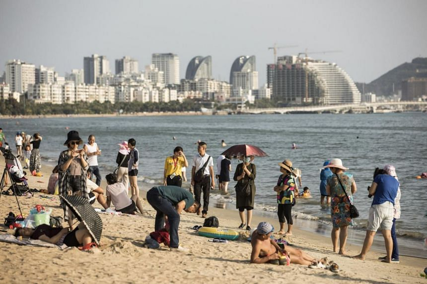 Tourists relaxing at Sanya Bay beach as buildings stand along the coast Hainan island in China on March 13, 2018.