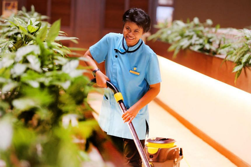 Pan Pacific Hotel guest service agent Noramira Mohd Amin, who has intellectual disabilities, working in the public area at Pan Pacific hotel on July 20, 2017.