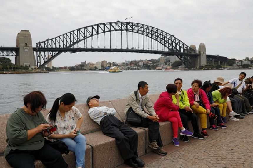 Chinese tourists rest near the Harbour Bridge in Sydney on April 18, 2018.