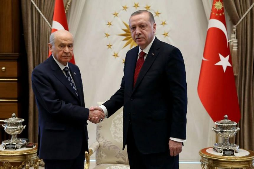 Turkish President Recep Tayyip Erdogan (right) shakes hands with Devlet Bahceli, leader of the Turkish National Movement Party (MHP), during their meeting at the Presidential Complex in Ankara on April 18, 2018.