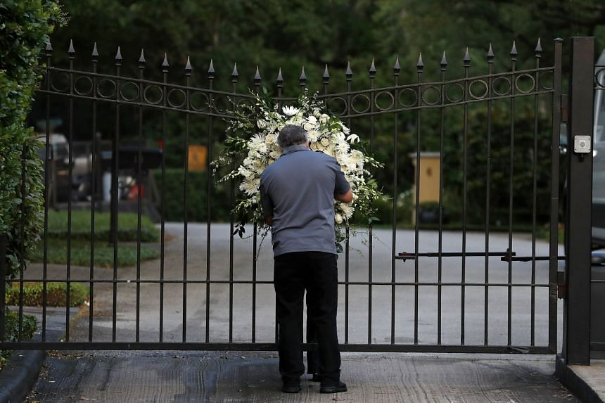 An employee hangs flowers outside the Texas gated community where former first lady Barbara Bush lived.