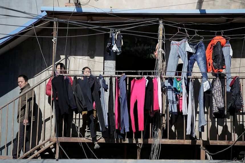 People at a low-cost dwelling in a village in the Tongzhou district of Beijing. The city had a permanent population of 21.7 million last year, but only 13.59 million held a Beijing hukou. Many migrant workers are marginalised and pay more for public