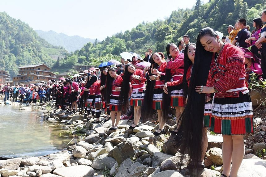 Women of the Yao tribe, an ethnic minority in China, grooming themselves by the river in Huangluo Yao village in Guilin, Guangxi in southern China, as part of their celebration of the Double Third Festival yesterday. The Yao women, known for their tr