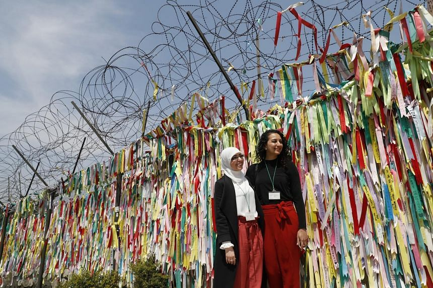 """Tourists posing for pictures at a fence covered with ribbons in Imjingak park near the Demilitarised Zone in Paju, in South Korea's Gyeonggi-do province, yesterday. A senior Blue House official said Seoul is """"looking at the possibility of replacing t"""