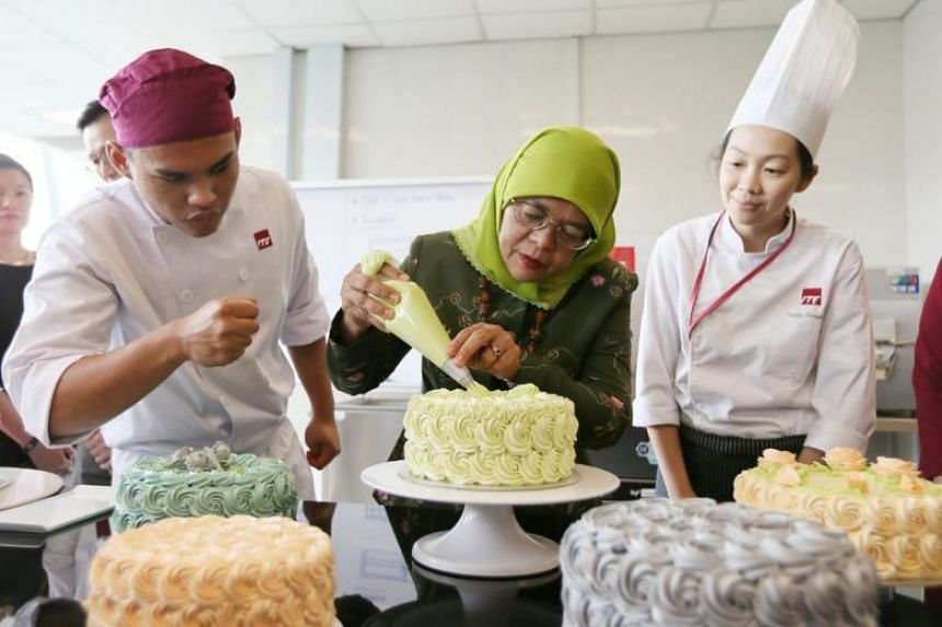 President Halimah Yacob piping a rosette on a buttercream cake, as pastry and baking student Mohammad Ghazi, 17, and lecturer Tanty Suryani, 36, look on at ITE College West on April 18, 2018.