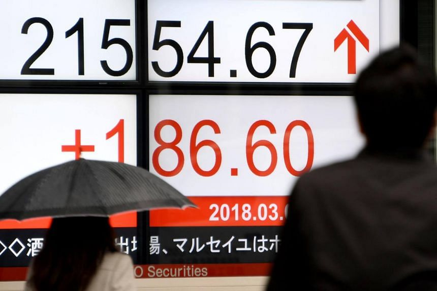 Pedestrians walk past an electronics stock indicator at the window of a securities company in Tokyo, on March 9, 2018.