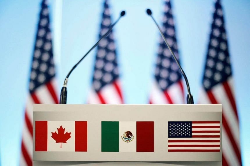 The flags of Canada, Mexico and the US are seen on a lectern before a joint news conference on the closing of the seventh round of NAFTA talks in Mexico City, Mexico, on March 5, 2018.
