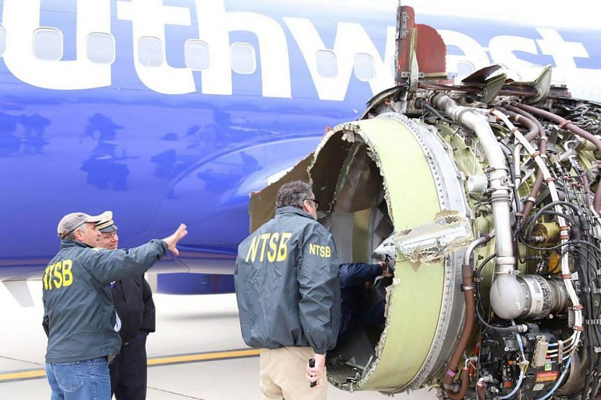 US National Transportation Safety Board investigators on scene examining damage to the engine of the Southwest Airlines plane on April 17, 2018.