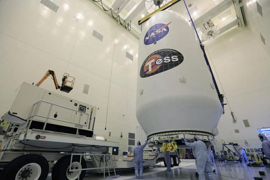 The SpaceX payload fairing containing the Nasa's Transiting Exoplanet Survey Satellite (TESS) is moved by crane to a transporter inside the Payload Hazardous Servicing Facility at Nasa's Kennedy Space Center, Florida on April 11, 2018.