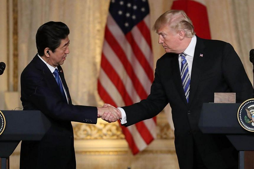 US President Donald Trump (right) looks on as Japan's Prime Minister Shinzo Abe speaks while dining at Trump's Mar-a-Lago estate in Palm Beach, Florida, on April 18, 2018.