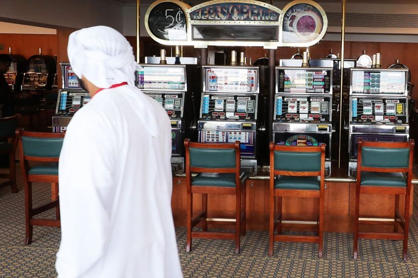 A man walks past disused slot machines in the gaming arcade of The Queen Elizabeth II luxury cruise liner.