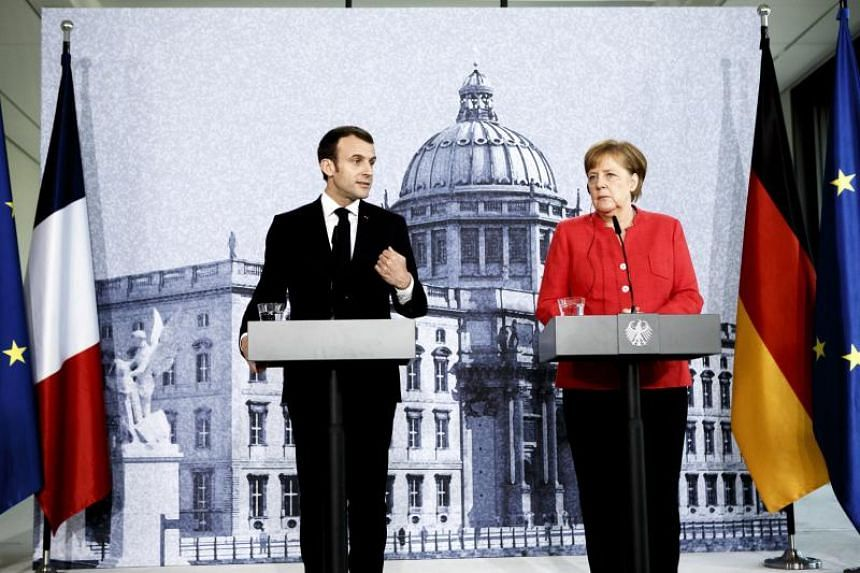 German Chancellor Angela Merkel (right) and French President Emmanuel Macron hold a press conference following a visit at the Humboldt Forum construction site in Berlin, Germany, on April 19, 2018.