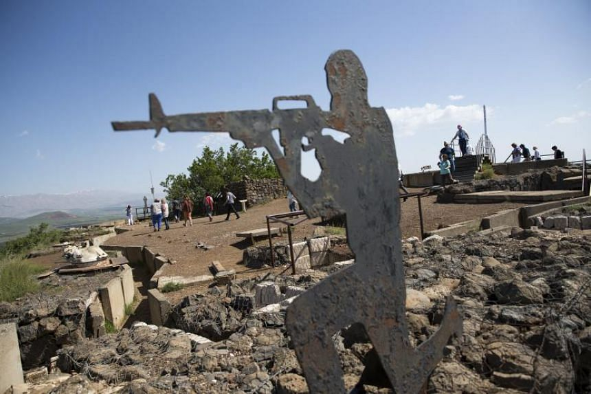 Tourists walk past the statue of an Israeli soldier next to the Israeli-Syrian border in the Golan Heights on April 14, 2018.