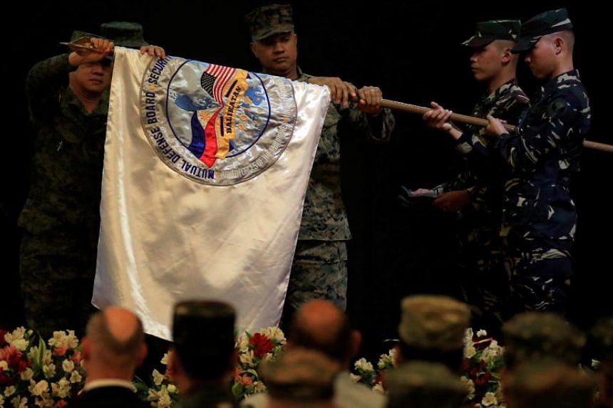 The Philippine military's Major-General Herminigildo Francisco Aquino (left) with US Marines Brigadier-General Brian Cavanaugh (centre) furling the Balikatan flag in Quezon city, Metro Manila, Philippines, on May 19, 2017.