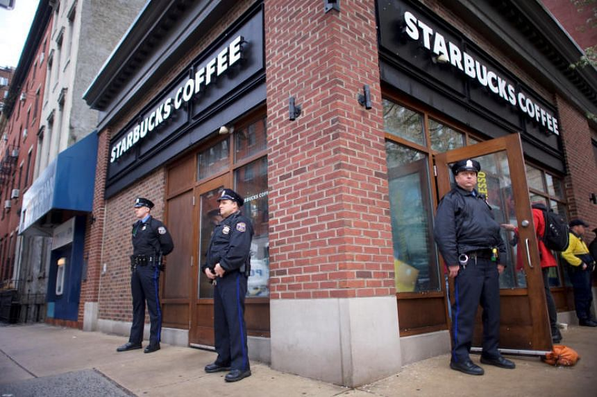 Police officers monitor activity outside as protesters demonstrate inside a Center City Starbucks, where two black men were arrested, in Philadelphia, Pennsylvania, on April 16, 2018.