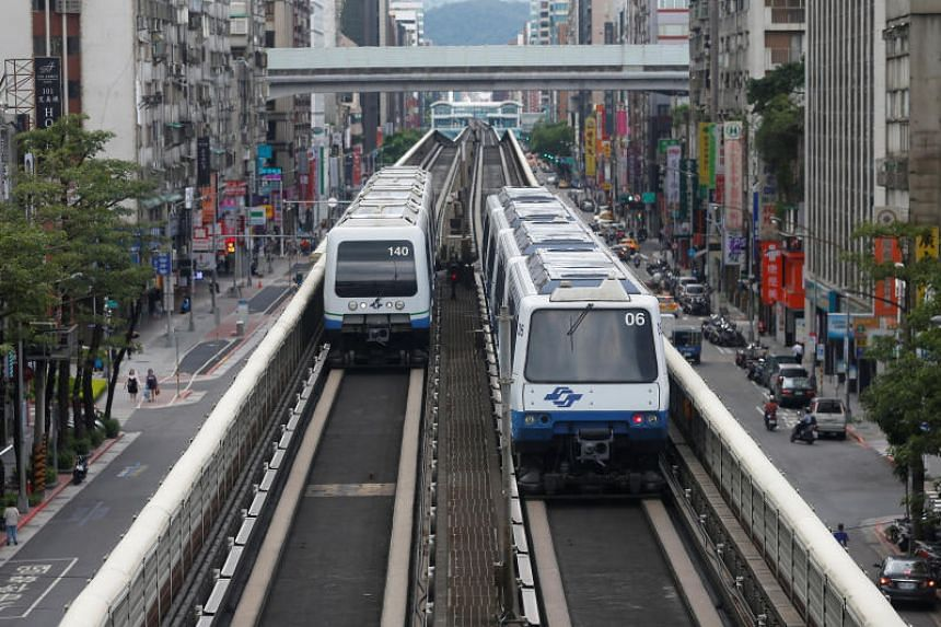 Trains operated by Taipei Rapid Transit pass residential buildings in Taipei on July 6, 2017.