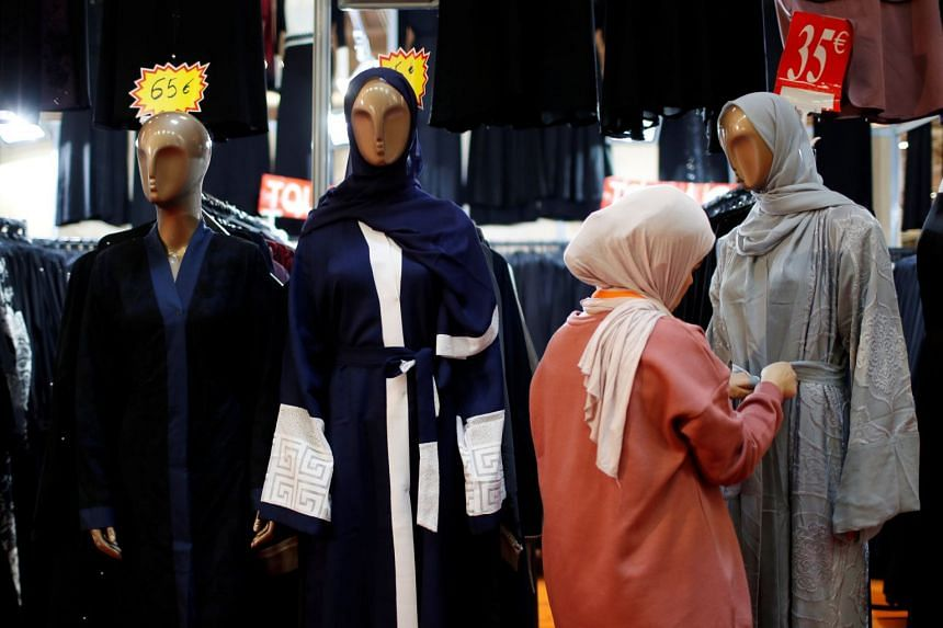 A visitor checks out clothing at a cultural event for French Muslims near Paris, on March 30, 2018.