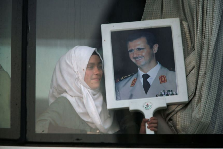 A Syrian refugee who fled to Lebanon holds a picture of Syrian President Bashar Al-Assad.