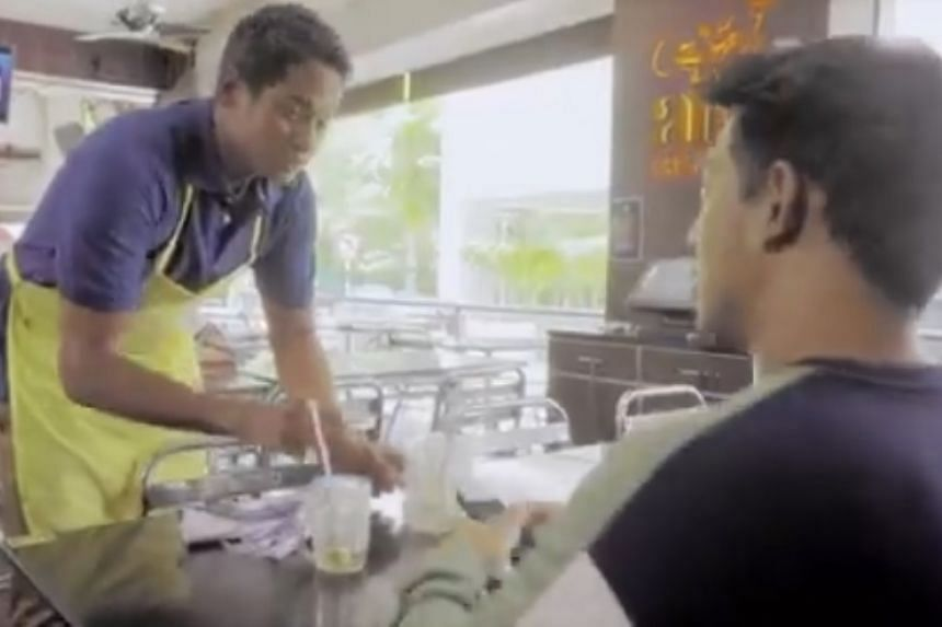 Wearing a dark blue polo and a yellow apron, Malaysia's Youth and Sports Minister Khairy Jamaluddin is seen taking and delivering orders, and cleaning tables in his latest acting role.