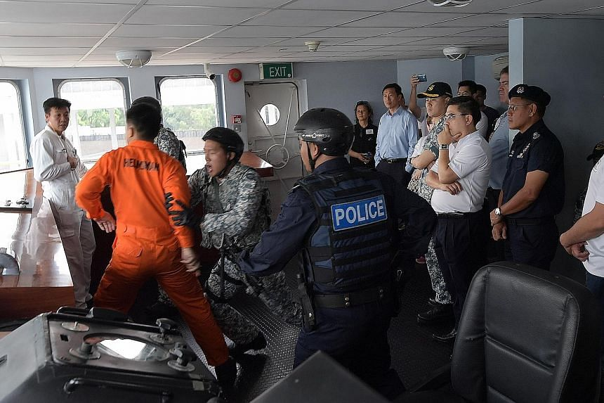 Left: Mr Ong Ye Kung (in blue shirt) and members of the Advisory Council on Community Relations in Defence watching a demonstration of 180 Squadron members handling a hostile situation yesterday. Below: Corporal Warren Ng climbs a rope ladder to boar