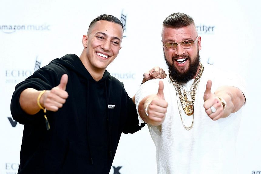 """Prince Harry and Meghan Markle were set up on a blind date by a mutual friend and they hit it off instantly. In their album last year, German rappers Farid Bang (far left) and Kollegah boasted about how their bodies are """"more defined than Auschwitz p"""