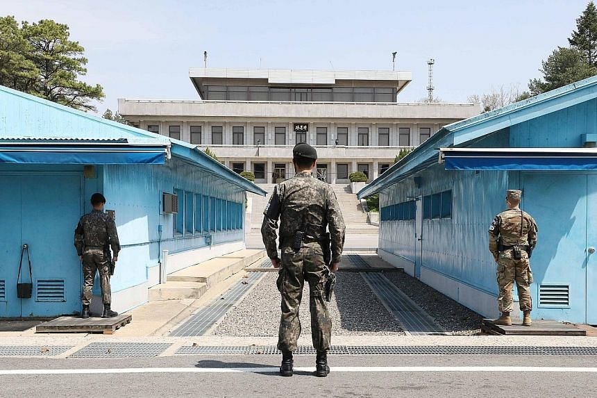 South Korean and US soldiers on guard at the inter-Korean truce village of Panmunjom, the venue for talks between South Korea's President Moon Jae In (top) and the North's leader Kim Jong Un next Friday.