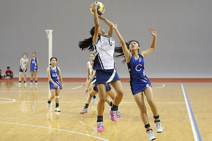 CHIJ Secondary (Toa Payoh) captain and centre Seraphina Low catching the ball cleanly, as her St Hilda's opponent Cheryl Tang fails to intercept the pass. CHIJ won the C Division netball title 33-23.