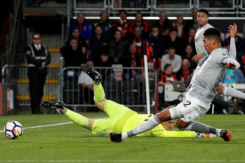 Manchester United's Chris Smalling sliding in to convert a lay-off from Jesse Lingard and score the opener against Bournemouth at Dean Court. United bounced back from their weekend loss to win 2-0 and consolidate second place in the Premier League, f