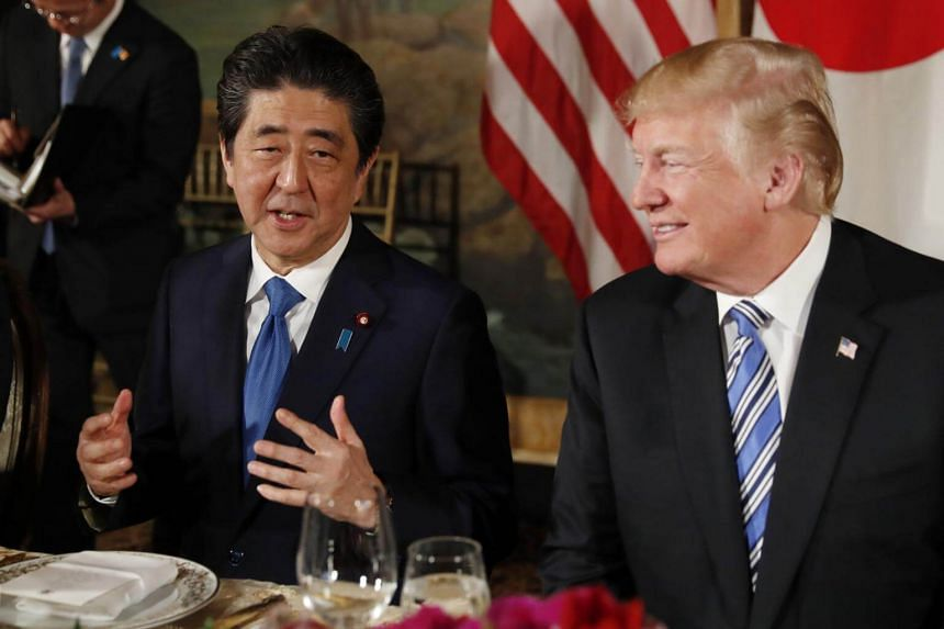 US President Donald Trump (right) looks on as Japan's Prime Minister Shinzo Abe speaks while dining at Mr Trump's Mar-a-Lago estate in Palm Beach, Florida, on April 18, 2018.