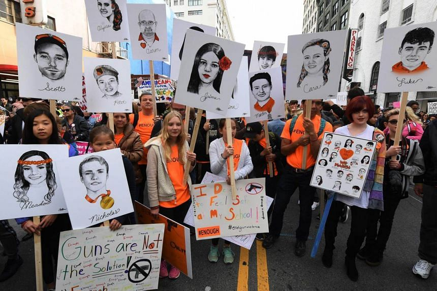 Students hold portraits of the victims of Florida's Marjory Stoneman Douglas High School shootings as people protest for tighter gun laws during the student-organised March For Our Lives rally in Los Angeles, California on March 24, 2018.