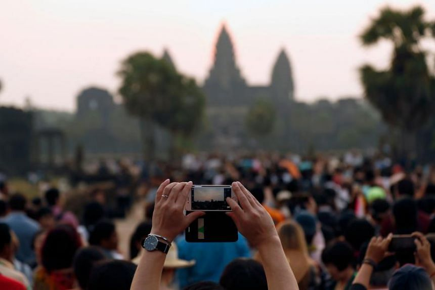 Visitors using their phones to take pictures of the sun rising over the central stupa of Angkor Wat temple in Siem Reap on March 22, 2018.