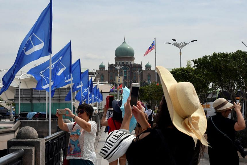 People take photos near flags of the ruling party, Barisan Nasional, in Putrajaya, Malaysia, on April 10, 2018.