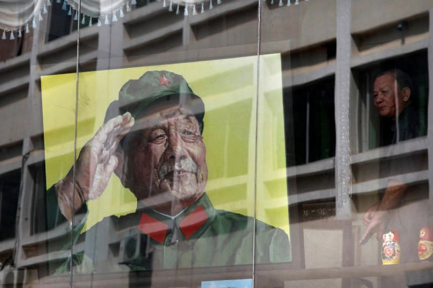 A man looks out from a window next to a portrait of late Chinese leader Deng Xiaoping in a gallery in Shenzhen, South China.