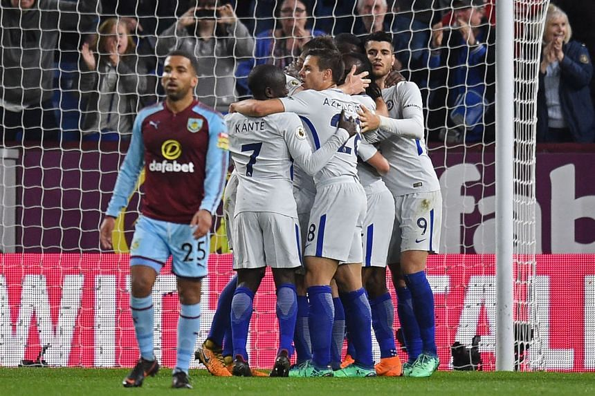 Cheslea players celebrate with midfielder Victor Moses (centre) after he scores their winning goal.