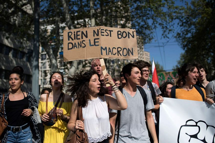 "A protester holds a placard reading ""Nothing is good in the Macron"" during a demonstration in Marseille."
