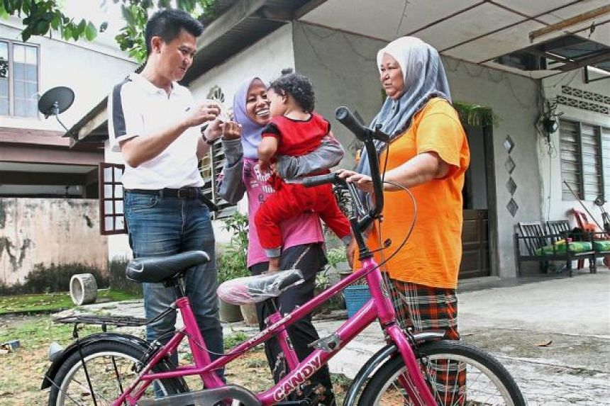 MCA Youth chief Datuk Chong Sin Woon (left) presenting the bicycle to Madam Shafarina Mohd Nasir and her daughter while neighbour Nor Haslimah (right) looks on.
