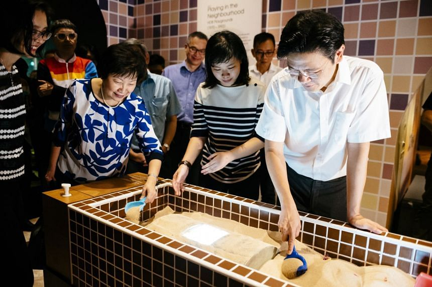 Minister for National Development Lawrence Wong penning his playground memories at the memory wall of The More We Get Together exhibition.