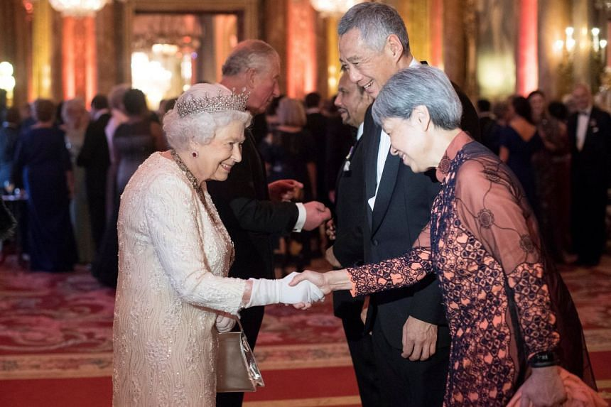 Queen Elizabeth greets PM Lee Hsien Loong, and his wife Madam Ho Ching, in the Blue Drawing Room at Buckingham Palace as she hosts a dinner during the Commonwealth Heads of Government Meeting, on April 19, 2018.