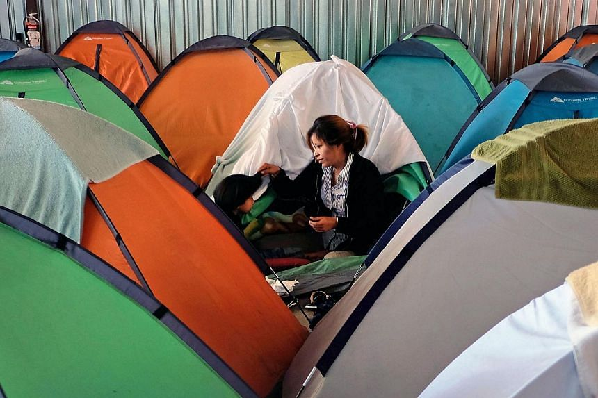 A Central American migrant with her daughter during the Migrant Via Crucis caravan outside their tent at a shelter in Tijuana, Mexico on April 17, 2018.