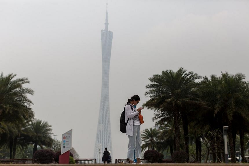 A woman using her mobile phone in front of the Guangzhou Tower in Guangzhou, China on April 19, 2018.