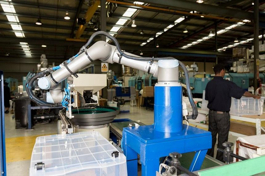 Workers work alongside collaborative robots (cobots) which are used for precision machining and contract manufacturing services for the medical device industry at Tegra Medical in the US.