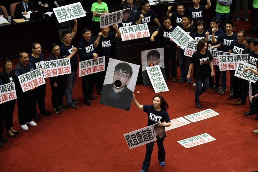 A lawmaker of the Kuomintang displays a portrait of Tuan Yi-kang, a legislator from the ruling Democratic Progressive Party, during a protest at the Parliament in Taipei on April 20, 2018.