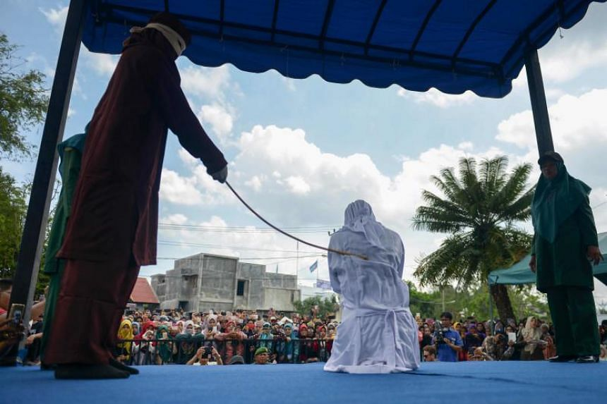 A woman is publicly flogged in front of a mosque in the provincial capital Banda Aceh on April 20, 2018.