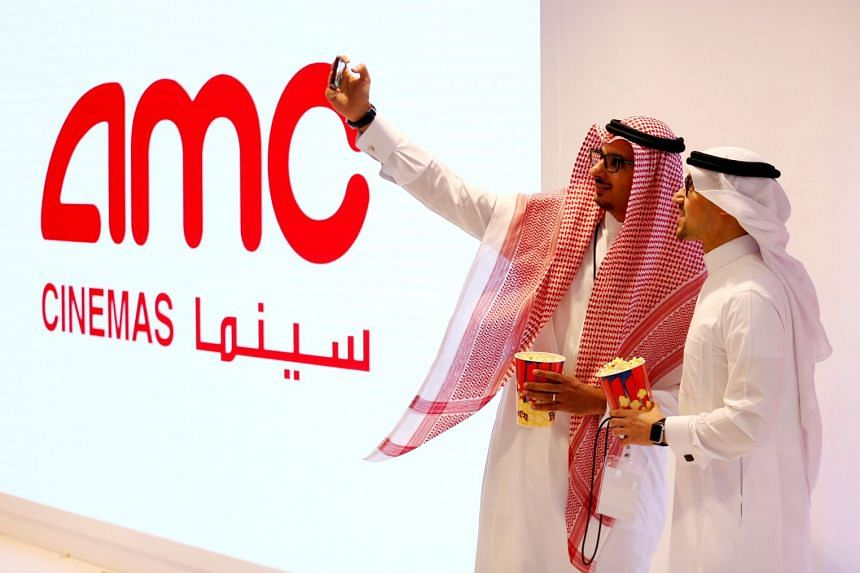 Two Saudi men take a selfie at Saudi Arabia's first commercial movie theatre in Riyadh, April 18, 2018.