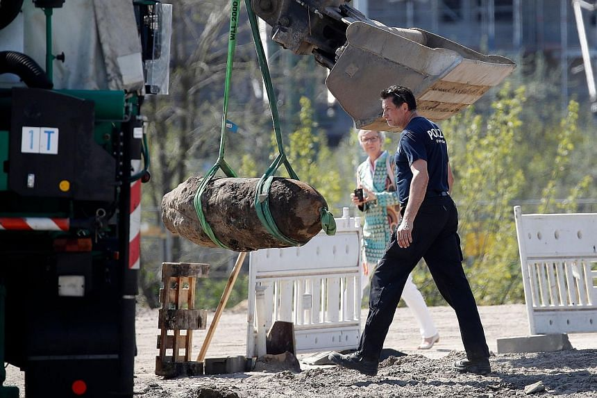 German police removing a 500kg World War II bomb found near Berlin's Hauptbahnhof main railway station. The disposal of the bomb yesterday resulted in evacuation of the train station, the Economy Ministry, a museum and part of a hospital. Train, bus
