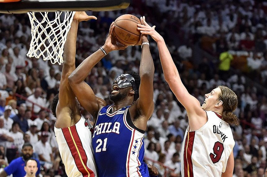 Joel Embiid of the Philadelphia 76ers drives to the basket while being defended by Hassan Whiteside (left) and Kelly Olynyk. Embiid scored 23 points in the Sixers' 128-108 win in Game 3.