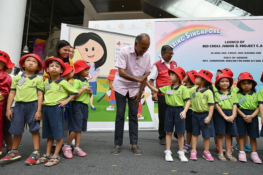 Law and Home Affairs Minister K. Shanmugam exchanging a high five with five-year-old Tan Ying Tong at Our Tampines Hub yesterday, at the launch of the Red Cross Junior club, a programme by the Singapore Red Cross and Kidz Meadow, which teaches five-t