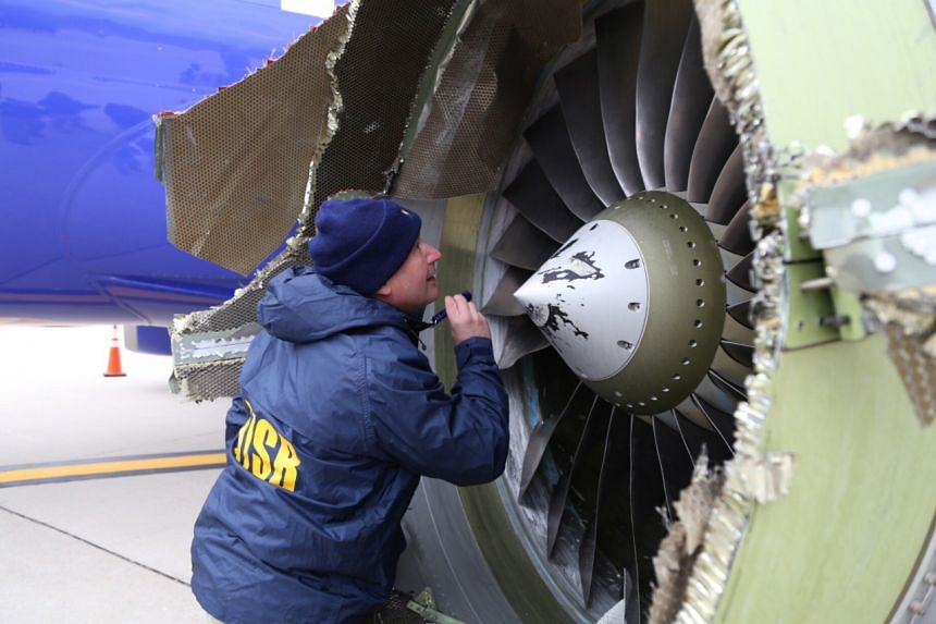 Investigators examine an engine on the Southwest Airlines plane.
