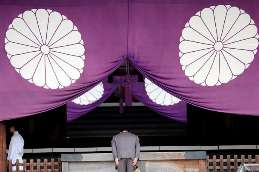 A visitor bows while paying tribute to the war dead during an autumn festival at Yasukuni Shrine in Tokyo, on Oct 17, 2017.